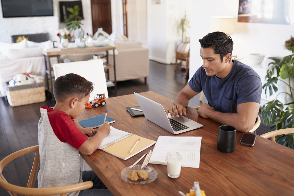 Hispanic father and son working opposite each other at the dining room table, elevated view